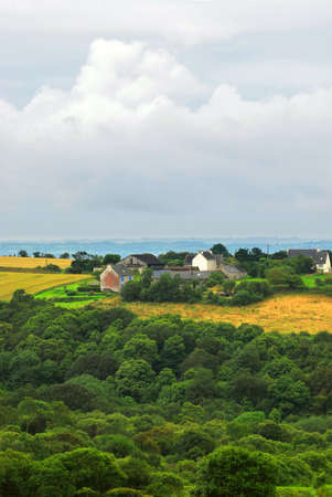 Scenic view on agricultural landscape with a farm house in rural Brittany, France photo