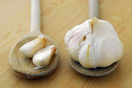 Bulbs and cloves of garlic on wooden cooking spoons