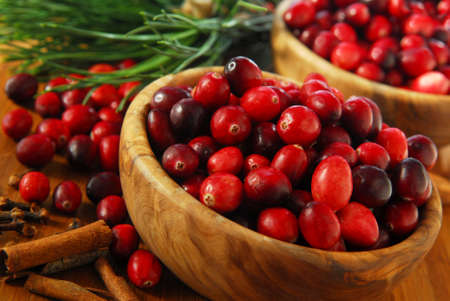 Fresh red cranberries in wooden bowls with spices and pine branches