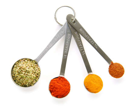 Assorted spices in measuring spoons on white background