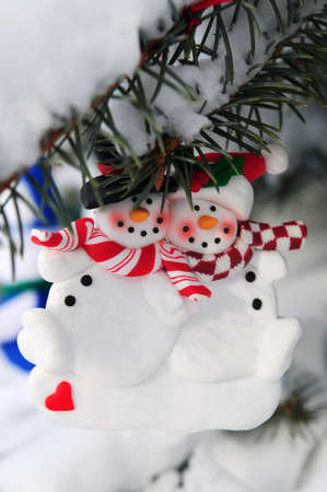 decorating christmas tree: Snowmen Christmas ornament hanging on snow covered spruce tree outside