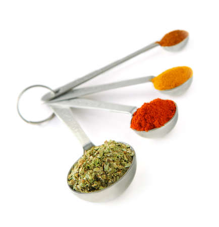 Assorted spices in metal measuring spoons on white background photo