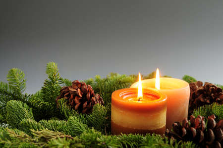 Christmas arrangement of burning candles and green spruce branches, background photo
