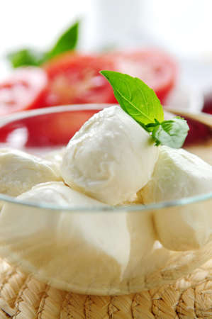 Bocconcini cheese, basil and sliced tomatoes - ingredients of traditional italian cuisine photo
