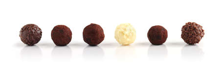 swiss ball: Row of assorted chocolate truffles on white background