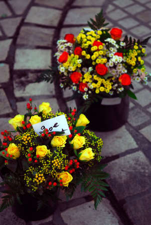 sidewalk sale: Bouquets of roses and other flowers on farmers market in Perigueux, France