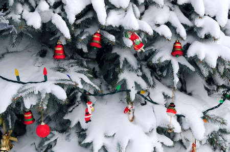 Christmas ornaments handing on snow covered spruce tree outside Stock Photo - 2368508