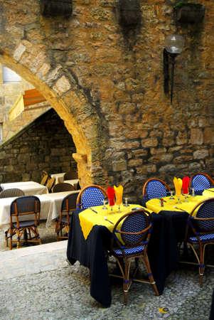 Restaurant patio among medieval walls in Sarlat, Dordogne region, France photo