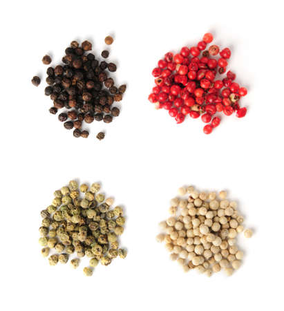 peppercorns: Heaps of assorted peppercorns on white background, top view Stock Photo