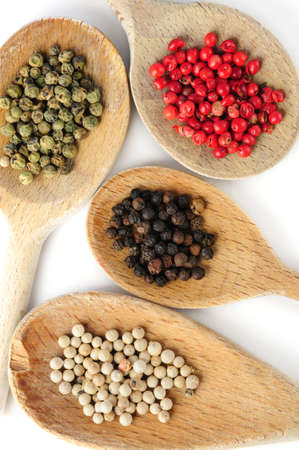 Four kinds of peppercorns in wooden cooking spoons photo