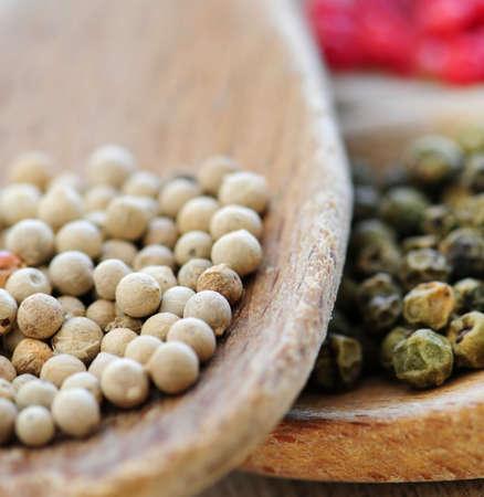 peppercorns: Assorted peppercorns in wooden cooking spoons macro Stock Photo
