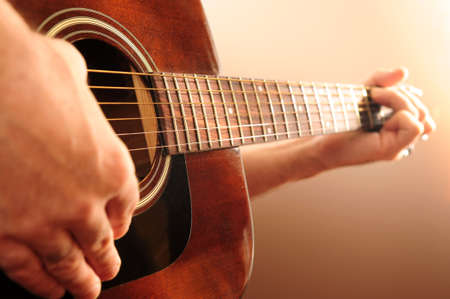 Hands of a person playing an acoustic guitar photo