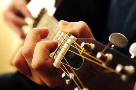 pegheads: Hands of a person playing an acoustic guitar close up