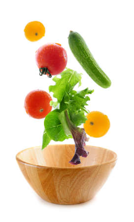 Assorted fresh vegetables falling into a wooden salad bowl isolated on white background photo