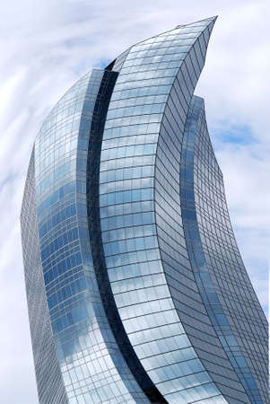 reflecting: Distorted futuristic corporate building with glass walls reflecting clouds