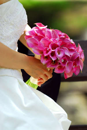wedding bouquet: Bride in wedding gown holding bouquet of pink flowers