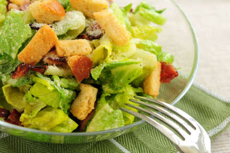 Fresh caesar salad with croutons and bacon bits served in a glass bowl photo