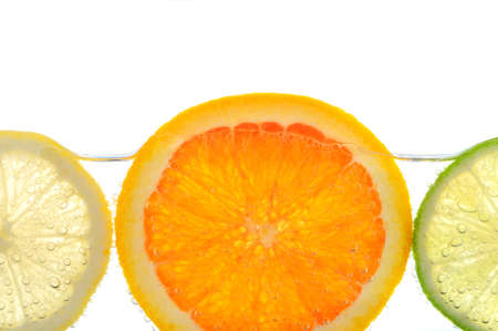 Orange lemon and lime slices in water with air bubbles on white background photo