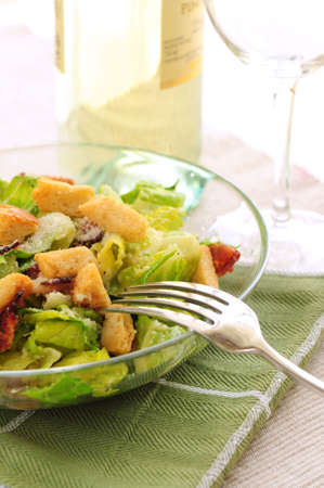 Caesar salad served in a glass bowl and white wine photo