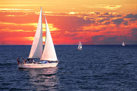 Sailboat sailing on a calm evening with dramatic sunset 版權商用圖片
