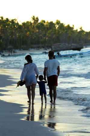 Family taking a walk on a sandy beach of tropical resort Stock Photo - 2853131