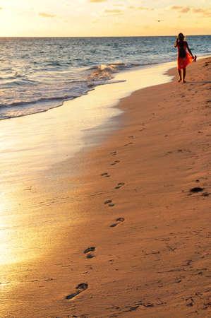 huellas de pies: Woman walking en playa tropical al amanecer