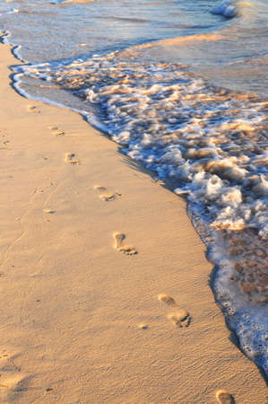washed: Footprints on sandy tropical beach washed away by waves Stock Photo