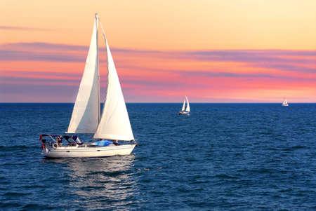 sailing: Sailboat sailing towards sunset on a calm evening Stock Photo