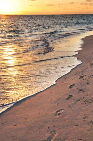 Footprints on sandy tropical beach at sunrise