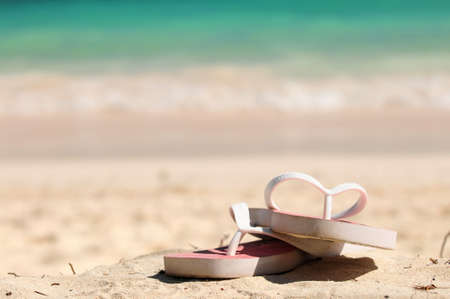 flops: Flipflops on a sandy ocean beach - vacation concept