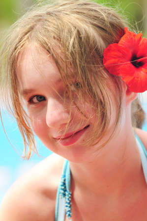 Portrait of a young girl on tropical beach with red flower photo
