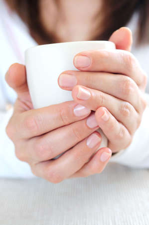 weekend break: Hands of a mature woman holding a cup