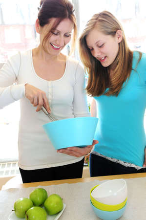 Mother and daughter cooking together at home photo