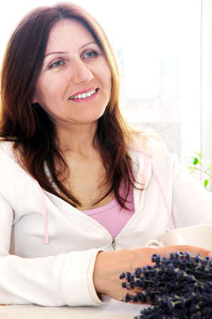 Smiling mature woman relaxing at home holding a cup Stock Photo - 2956617
