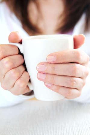 disfrutar: Las manos de una mujer madura la celebraci�n de una taza