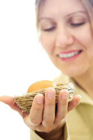 Mature woman holding a nest with an egg - investment concept Stock Photo - 2956491