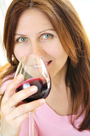 aging woman: Smiling mature woman holding a glass of red wine Stock Photo