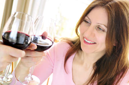 old people: Mature woman toasting with a glass of red wine