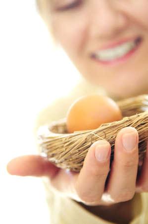 Coppia donna in possesso di un nido con un uovo - concetto di investimento  Archivio Fotografico