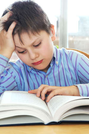 Serious school boy studying with a book Stock Photo - 3010113