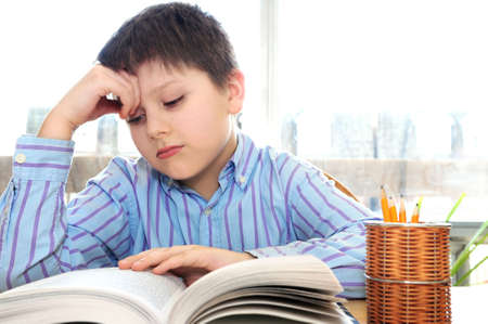Serious school boy studying with a book Stock Photo - 3010105