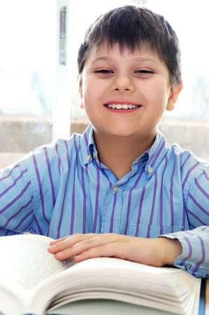 Feliz niño estudiando en la escuela un libro Foto de archivo - 3010112