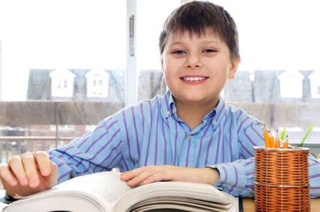 Happy school boy studying with a book photo