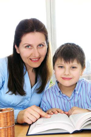 Teacher or tutor helping school boy to study photo