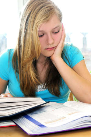 Teenage girl studying with textbooks looking unhappy photo
