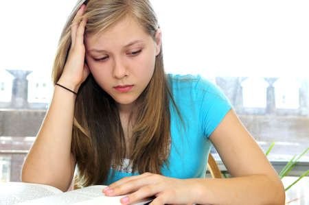 Teenage girl studying with textbooks looking unhappy Stock Photo - 3024900