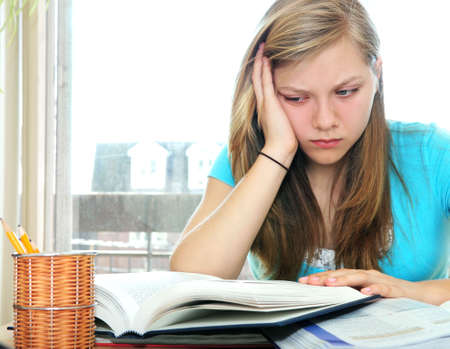 difficulties: Teenage girl studying with textbooks looking unhappy