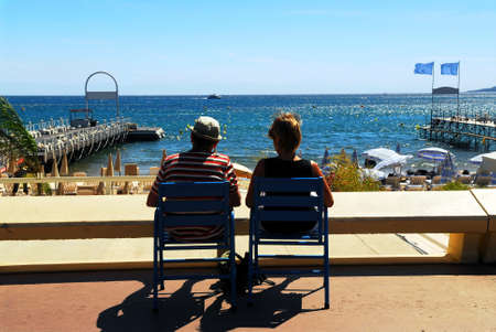 Couple relaxing in chairs on Croisette promenade in Cannes, France photo