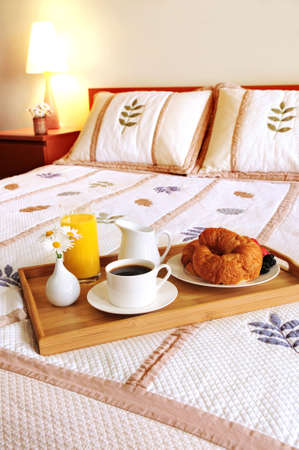hotel: Tray with breakfast on a bed in a hotel room