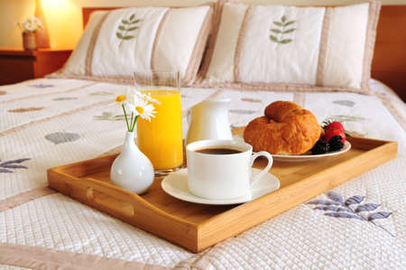 Tray with breakfast on a bed in a hotel room photo